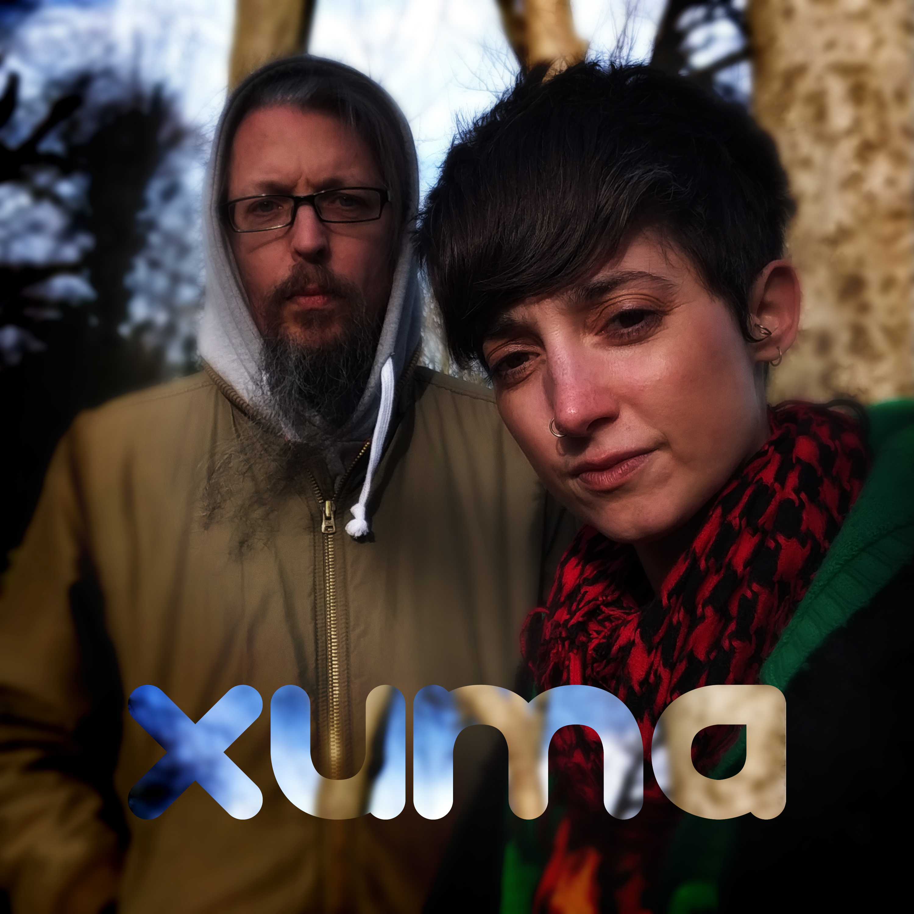 Xuma, Here We Are. A portrait of a couple, standing in the woods.